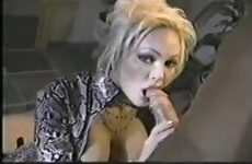 Wulps kijkend in de camera geeft ze de dikke lid een blowjob beurt