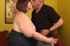 De dikke vrouw neemt de grote lul in haar mond en pijpt